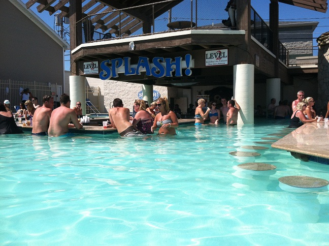 The front of the Splash Bar with people sitting in the stools in the water