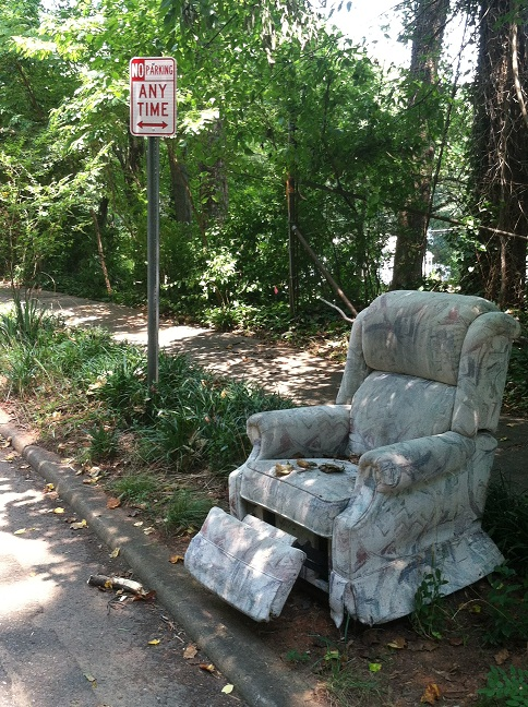 A recliner on the side of the road next to a 'No Parking' sign.