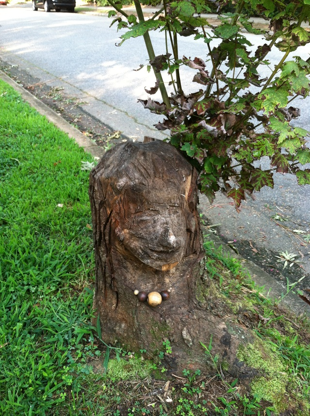 Tree stump with a face carved into it and a 'necklace' around it made out of various sizes of wooden beads.