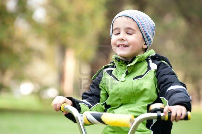 Little boy riding his bike with his eyes closed