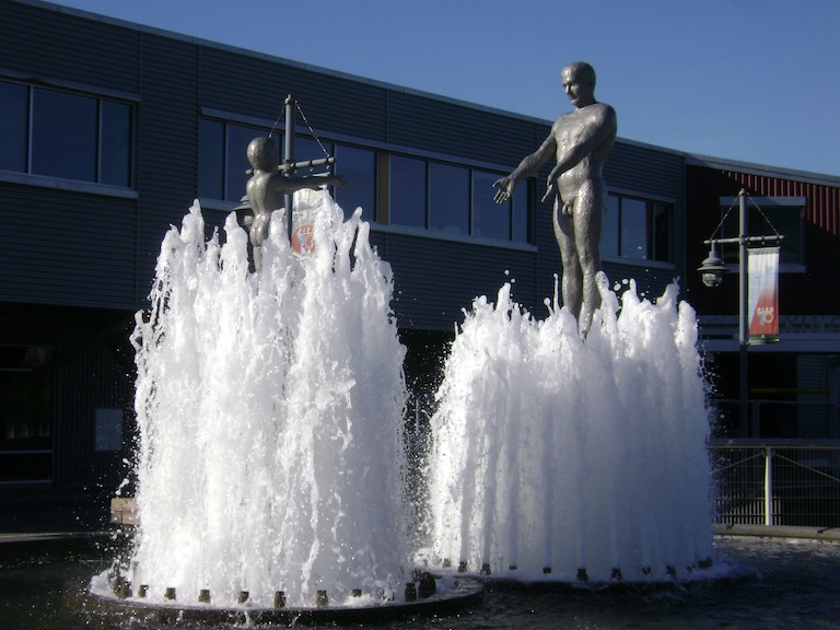 A naked man and boy in a fountain in which the water rises up from their feet and covers them at opposite times