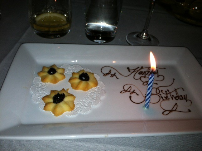hree cookies on a plate, a candle, and Happy Birthday written in chocolate