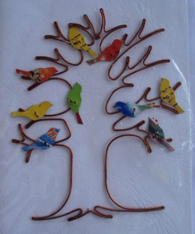 A card handmade in Kenya of a tree made out of wire with a bunch of birds in the branches