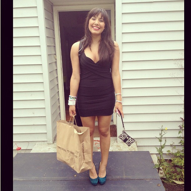 Attractive brunette standing in her doorway with a shopping bag in one hand and a little purse in the other