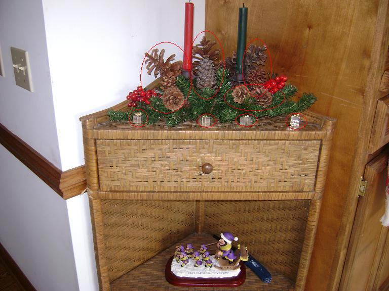Kitchen corner table with candles surrounded by greenery and pinecones and small presents in front of it