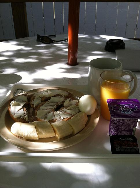 Bagel with cream cheese, a banana, a hard-boiled egg, orange juice, coffee, and yogurt