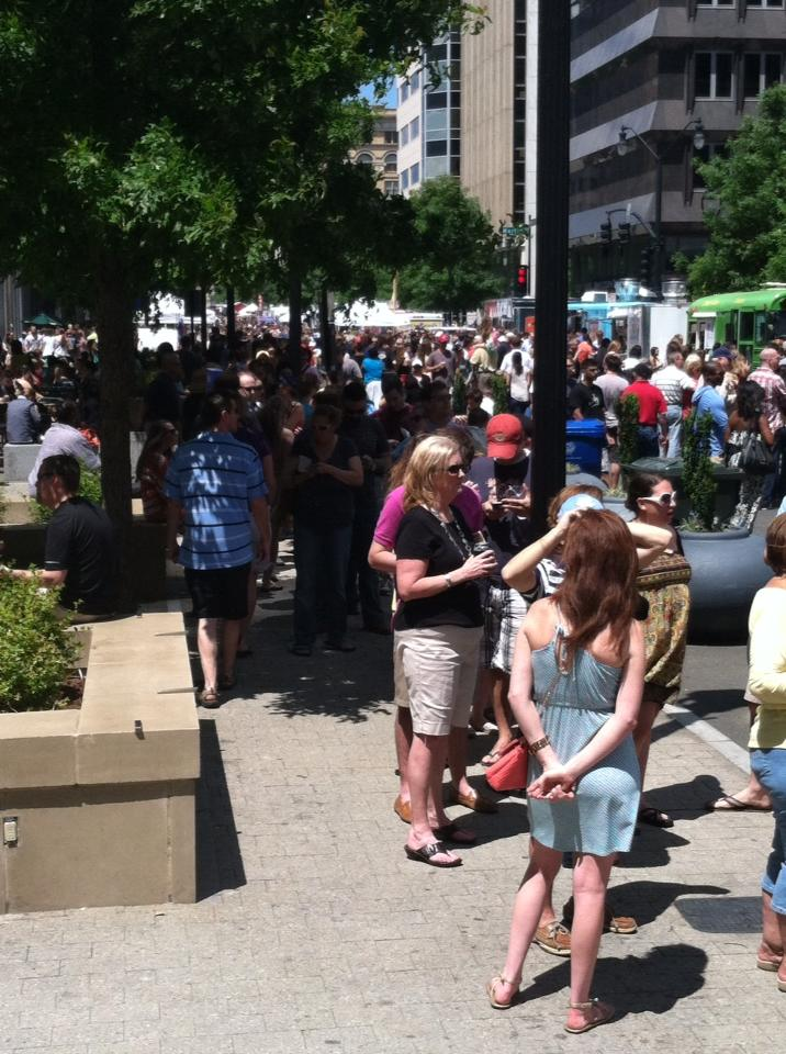 A view up Fayetteville Street, a couple of trucks, and the long lines of people waiting for them and/or milling about