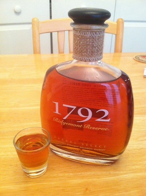 A shot glass full of 1793 bourbon beside its bottle