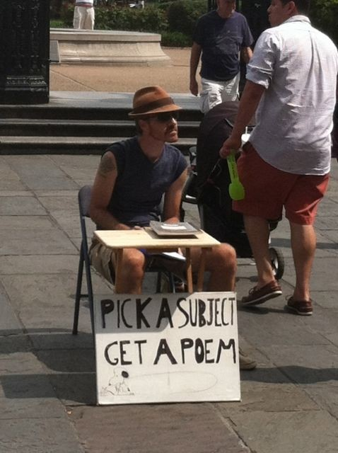 Guy sitting behind a 'Pick a subject, get a poem,' sign