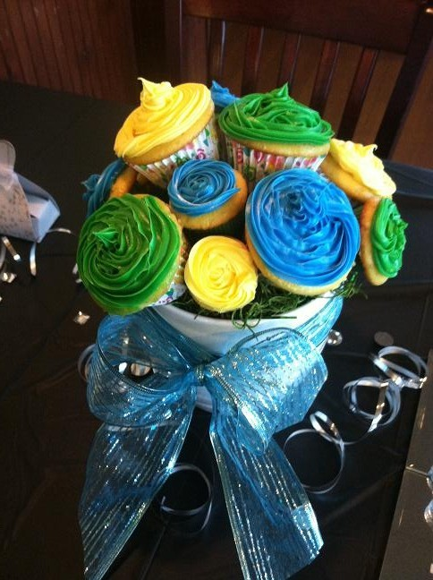 Green, yellow, and blue cupcakes on a skewer arranged like a bouquet