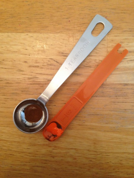 A plastic, 1/8 teaspoon, orange measuring spoon and a metal, 1 teaspoon measuring spoon.