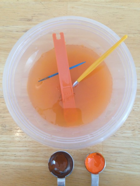 Plastic container with water, the plastic measuring spoon and the two brushes in it, and a 1-teaspoon measuring spoon with a brown paint mix in it and a 1/2-teaspoon one with an orange paint mix in it.