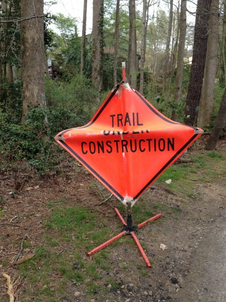 Sign beside trail that says trail under construction