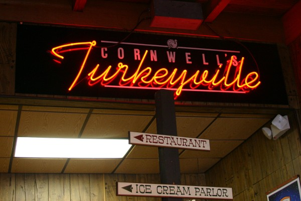 Cornwell's Turkeyville neon sign, with smaller wooden signs pointing toward the restaurant and the ice cream parlor