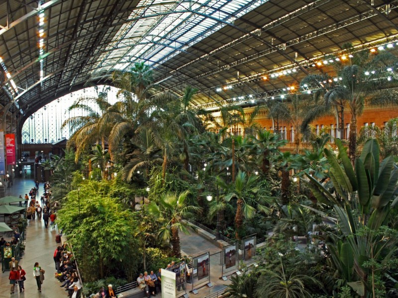 the-atocha-train-station-in-madrid-spain-is-the-citys-largest-and-includes-steel-and-glass-construction-blended-with-tropical-gardens-throughout-its-concourse-while-waiting-for-your-train-view-the-stations-display-of-sculptures