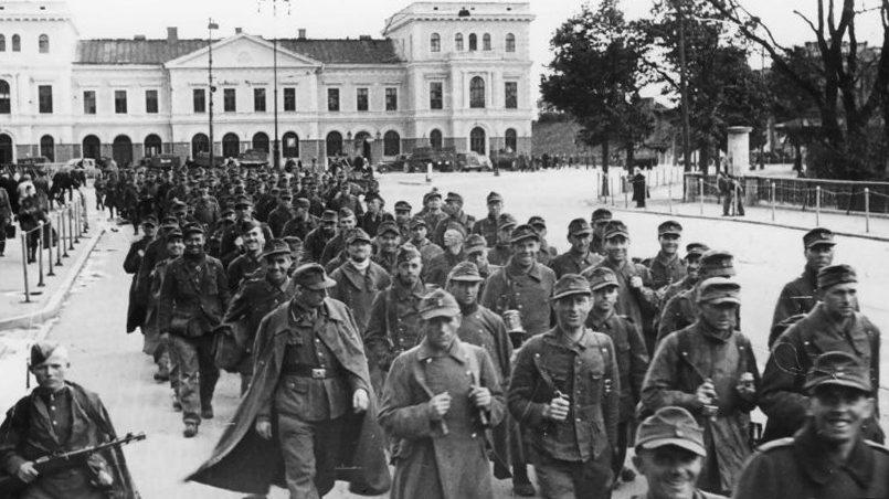 Источник изображения: Колонна немецких военнопленных проходит мимо железнодорожного вокзала Риги. В кадр попало здание старого вокзала Риги