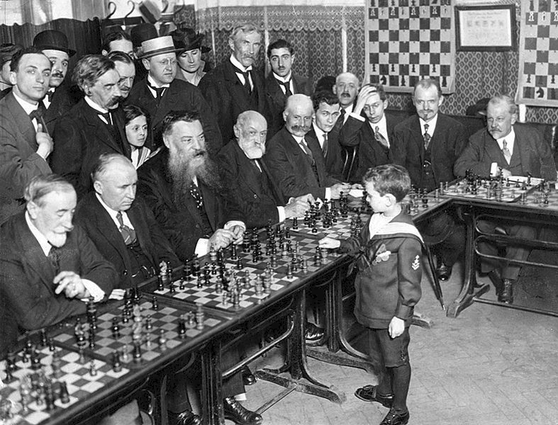 An eight-year-old Reshevsky performing a simultaneous exhibition in France. (The third gentleman from the right looks particularly shocked.) Image in public domain in United States.