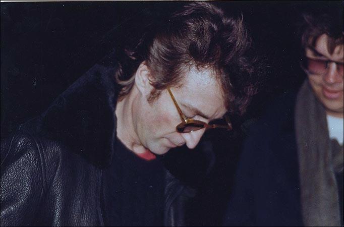 Джон Леннон даёт автограф своему убийце Марку Чепмену, сам Чепмен — человек на фото, стоящий сзади