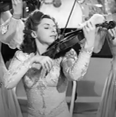 "Evelyn Kaye (""Evelyn and her magic violin"") plays with the Hour of Charm Orchestra (""Phil Spitalny and his All-Girl Orchestra"")."