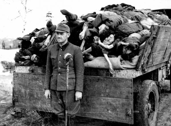 Бывший оберштурмфюрер СС Франц Хёсслер (Franz Hößler, 1906—1945) у микрофона перед грузовиком с телами узников концлагеря Берген-Бельзен.
