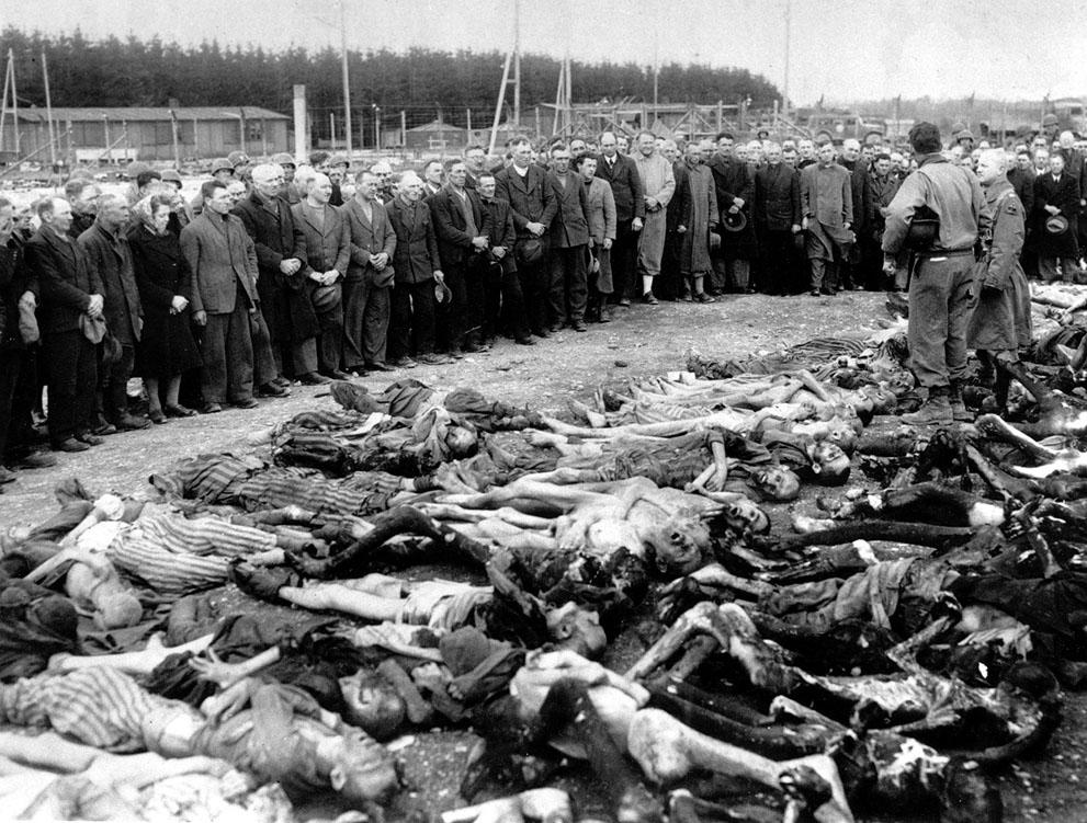 одполковник Эд Seiller в Луисвилле, штат Кентукки, стоит посреди кучи жертв Холокоста, в концентрационном лагере Ландсберг, 15 мая 1945 года.