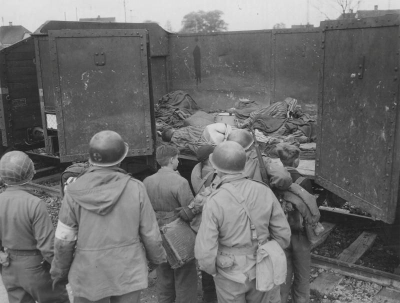 Солдаты 45-й американской пехотной дивизии показывают подросткам из «Гитлерюгенда» тела узников в вагоне в концлагере Дахау