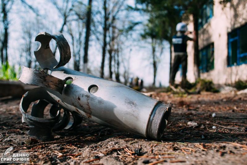 Снаряд ВСУ рядом с разрушенной школой в посёлке Зайцево. На фоне - сотрудник ОБСЕ фотографирует последствия обстрела. 2016