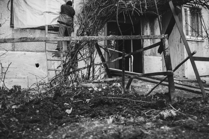 Житель посёлка Гольмовский закрывает плёнкой окно, выбитое в результате обстрела со стороны ВСУ, Зима 2017