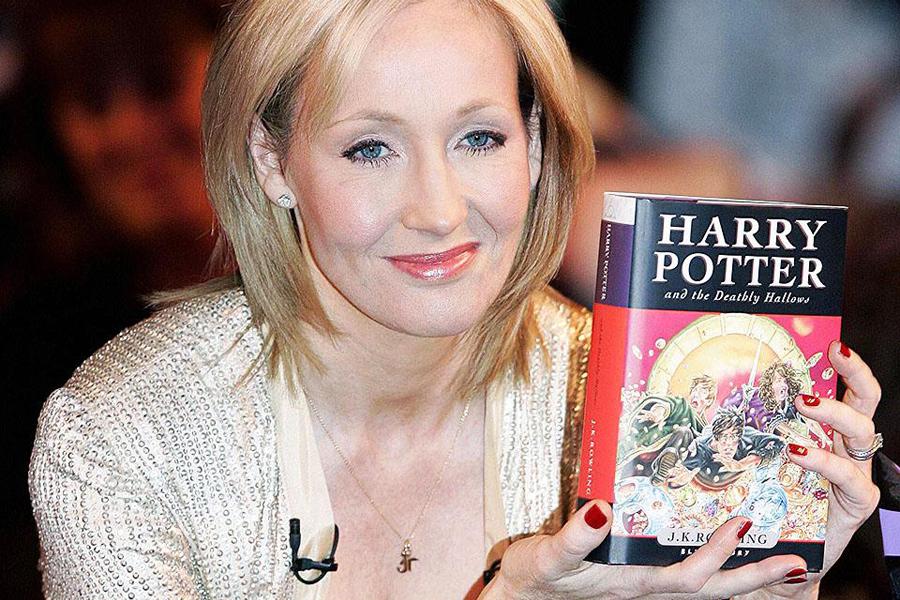 Джоан Роулинг с книгой «Гарри Поттер и Дары Смерти»