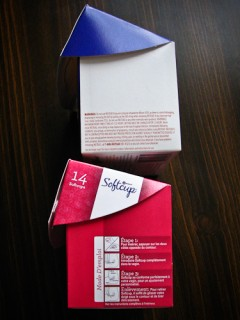 Two boxes of Instead Softcups. The top has the same warning about IUDs as on the left side, but in a different language. The bottom box has the same insertion diagram as on the left side, but in a different language.