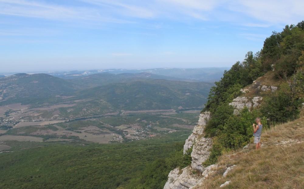 Здесь тоже были туристы, даже с детьми. Впрочем, несмотря на то, что именно по этой причине я предпочитаю ходить в горы по будням, это не мешало мне любоваться родными просторами Бельбекской долины и Крымских гор. Здесь, например, можно заметить КрАО и Тепе-Кермен с пещерными городами; ниже - Нагорное.