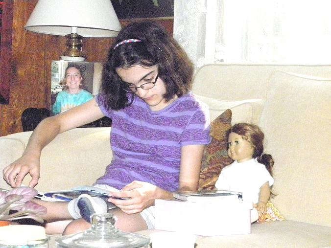 Sarah, age 13, with her American Girl doll and her knitting book