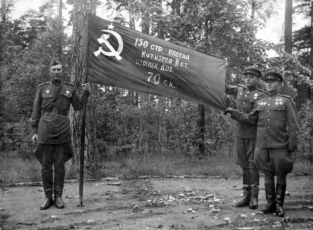 И.Я. Сьянов, В.И. Давыдов, Ф.М. Зинченко у развернутого знамени Победы.jpg