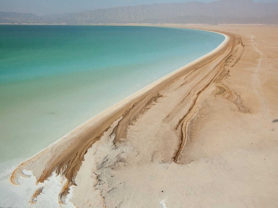 Озеро Ассал в Джибути – одно из самых соленых озер мира. Жара и сильный ветер способствуют интенсивному испарению влаги, оставляя кайму из минералов по берегу озера