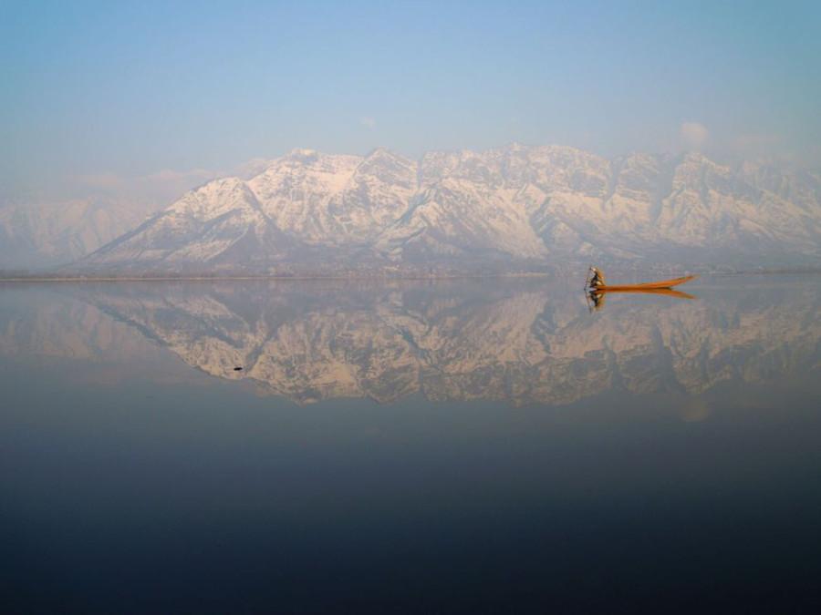 Озеро Дал, Индия. Одинокая лодка на тихих водах озера, в которых отражается горный хребет
