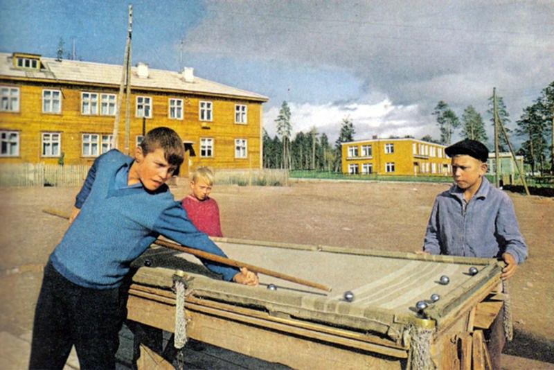 171 Мальчишки в Братске играют в бильярд, сделанный своими руками, и покрытый старым одеялом. Здание на заднем плане - одно из первых в Братске.jpg