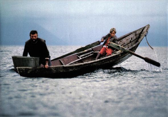 081 Рыбак Вячеслав Басов ставит сети, в то время как его сын, 10-летний Толя, управляет лодкой при помощи самодельных весел.jpg