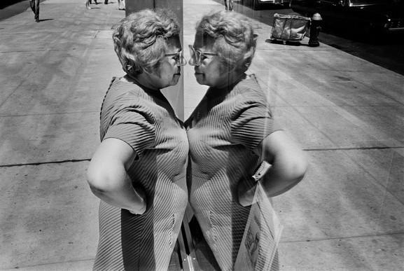 Richard Kalvar Woman looking at herself in store window