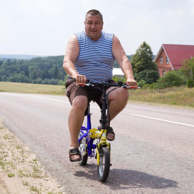 крупный мужчина на маленьком велогибриде