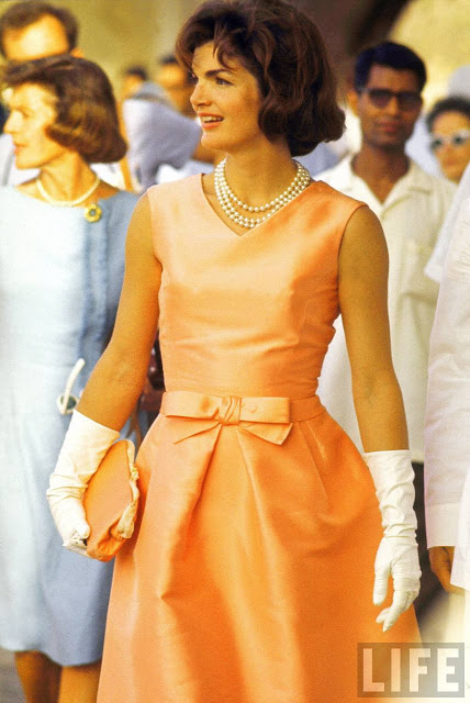 First Lady Jackie Kennedy, wearing a fitted silk apricot dress by designer Oleg Cassini and triple strand of pearls, walking through crowd in Udaipur during a visit to India