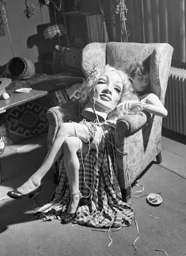 Young artist falls asleep with papier maché mask of Marlene Dietrich on her lap, 1950