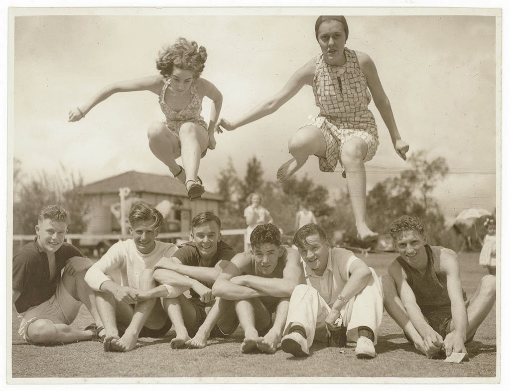 Girls jump over boys seated on a sportsground, c. 1930s, by Sam Hood