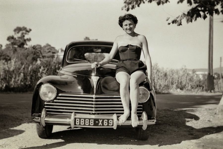 A young lady in a one-piece bathing suit posing on the bonnet of a black Peugeot 203, ca. 1951