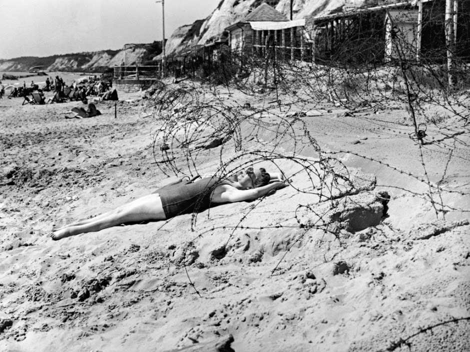 A woman sunbathes on Bournemouth beach on her August bank holiday in 1944, surrounded by tangles of barbed wire, 1944