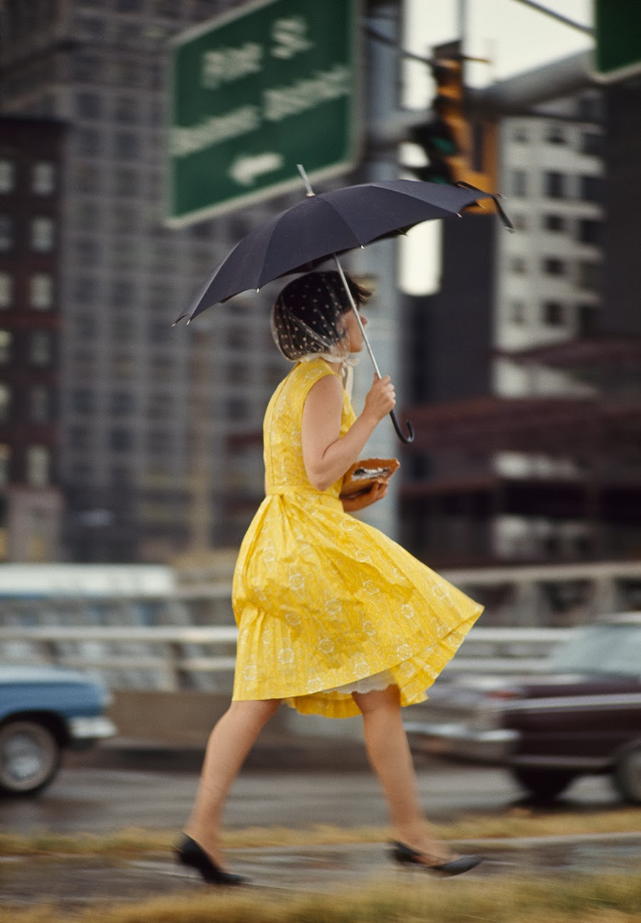 A woman in a yellow dress uses an umbrella to keep dry in Saint Louis, Missouri, November 1965