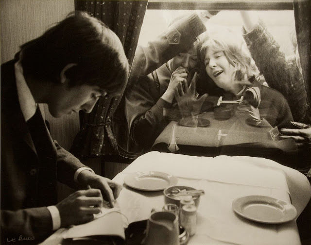 George Harrison writing autographs for fans. London, 1964