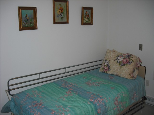 Mom's new place was furnished, so I couldn't bring much of her own furniture. Standard-issue hospital bed. The paintings on the wall are some that she did when she was younger.