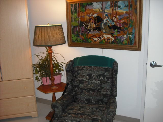 I refer to this as Mom's corner: her floor lamp, her favorite chair, and another painting (Falcon Hunt) that she did when she was younger. This little spot really warms up the room and makes it more inviting and less clinical.