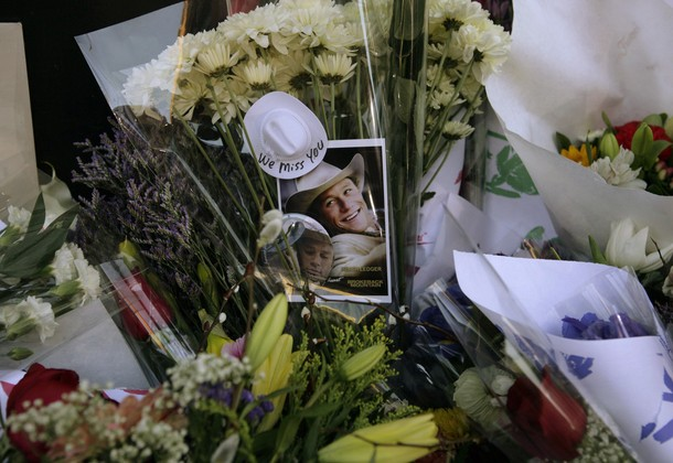"""A photograph of Heath Ledger from the movie """"Brokeback Mountain"""" rests among flowers at a makeshift memorial in front of the building where the actor died in New York January 23, 2008."""