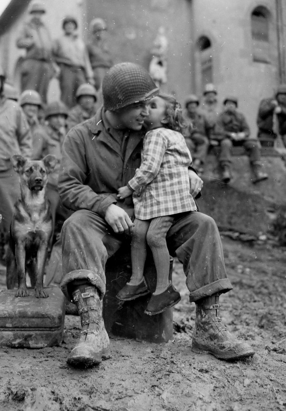 US Army Signal Corp Photo Tec-4 Elvin Harley getting a kiss from a French child while listening to the US 9th Armored Division Band near Aboncourt, France, 14 Feb 1945 Photo L. G. Crabtree